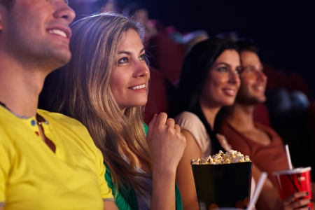theater popcorn: Young woman sitting in cinema, watching movie, smiling.