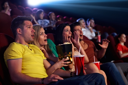 horror movies: Audience sitting in multiplex movie theater, watching horror movie, screaming.