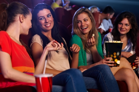 Pretty young girls sitting in auditorium of cinema, talking, smiling, eating popcorn. photo