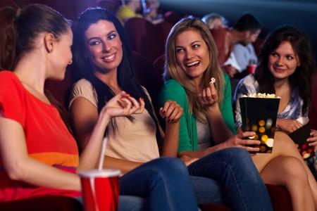 cinema people: Pretty young girls sitting in auditorium of cinema, talking, smiling, eating popcorn.