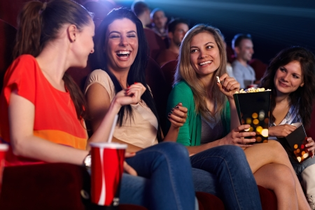 movies: Happy girls sitting in multiplex movie theater, talking, laughing. Stock Photo