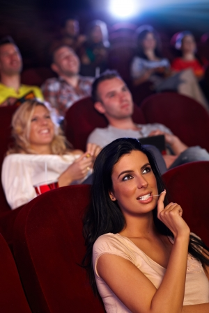 concentrating: Pretty young girl sitting in multiplex movie theater, watching movie, playing with chewing gum.