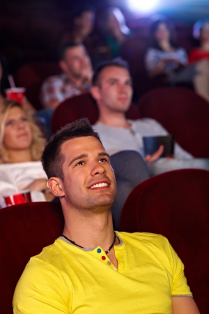 Young man sitting in multiplex movie theater, watching movie, smiling. photo