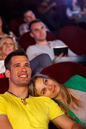 Romantic young couple sitting in cinema, watching movie, smiling. photo