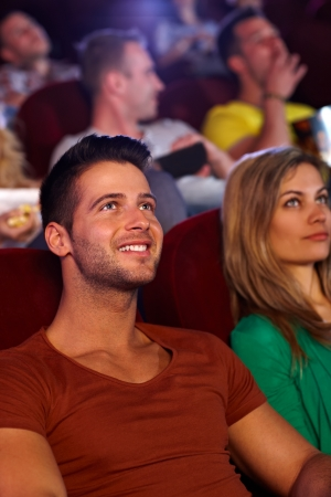 Closeup portrait of handsome young man sitting at movie theater, smiling. photo