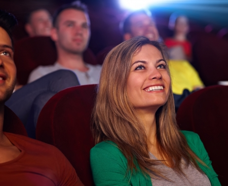 spectator: Closeup portrait of attractive young woman in cinema, watching movie, smiling.