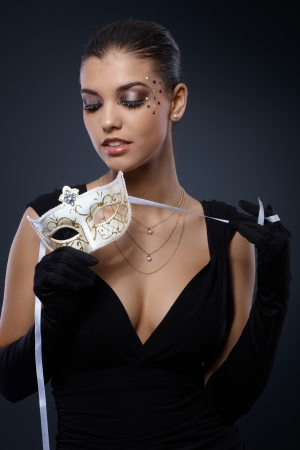 Beauty in smart black dress with carnival mask and party makeup. photo