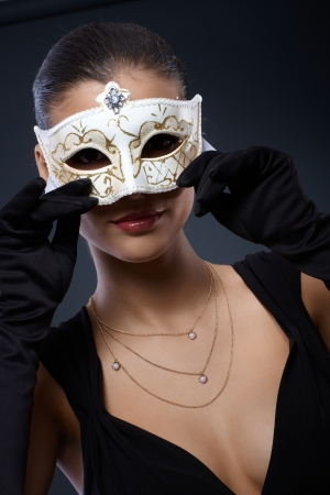 eye mask: Woman in elegant black dress hiding in decorated carnival mask, seductive smile.