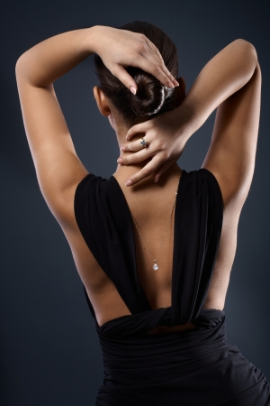 Attractive female back in black dress, sexy pose, hands on neck and hair, necklace visible. photo