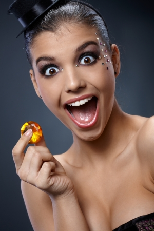 surprise face: Attractive woman excited, screaming in shock by sparkly gem handheld. Stock Photo