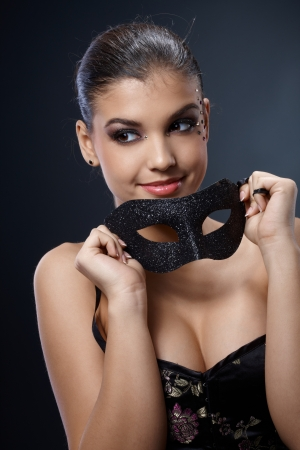 Attractive woman smiling happily in elegant sexy top with carnival mask handheld. Stock Photo - 15784440
