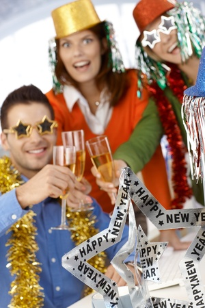 office party: Office workers celebrating new year wearing funny party accessories.