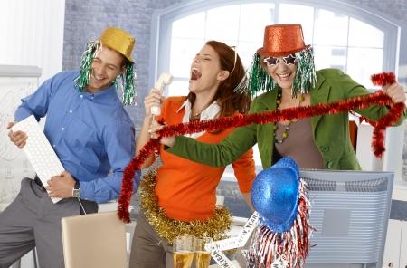 vibrant colors fun: Festive nuovo ufficio festa anno, gli impiegati che hanno divertimento con gli accessori. Archivio Fotografico