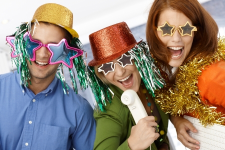 women having fun: New year celebration in office, office workers in party hat and funny sunglasses having fun. Stock Photo