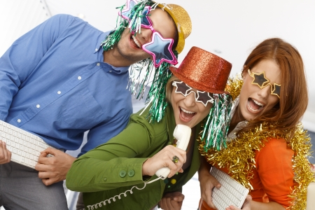 to sing: Joyful new years eve office band, workers using phone and keyboard as instrument, singing, having fun in party accessories.