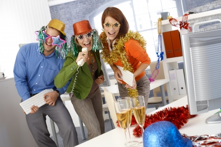 funny image: Funny new year eve party in office, businesspeople singing dancing with office tools, wearing festive party hat and glasses.