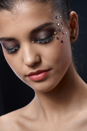glitter makeup: Closeup facial portrait of attractive young woman wearing elegant glittering makeup with strasses, eyes closed. Stock Photo