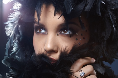 black boa: Beauty in elegant makeup with rhinestones hiding in feather boa, looking up.