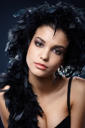 Attractive woman posing with black feather boa over head and neck, looking at camera. Stock Photo - 15784433