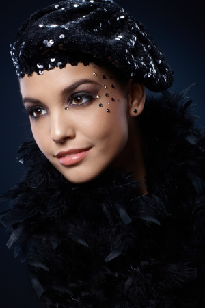 rhinestones: Portrait of beauty smiling in black sequin party hat and boa, with glamorous makeup of rhinestones. Stock Photo