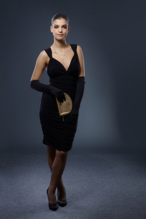 Full length portrait of pretty woman in smart black evening dress with gloves and handbag, smiling. Stock Photo - 15784422
