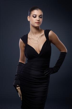 cocktaildress: Portret van aantrekkelijke vrouw in stijlvol zwart cocktail jurk en handschoenen.