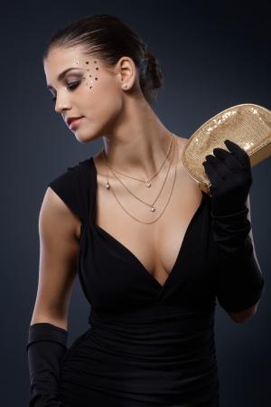 bonsoir: Beaut� habill�s pour la f�te �l�gante posant en robe noire avec sac � main et des gants d'or parti, maquillage glamour avec strass.