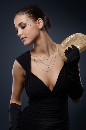 cleavage: Beauty dressed for elegant party posing in black dress with golden party handbag and gloves, glamorous makeup with strasses. Stock Photo