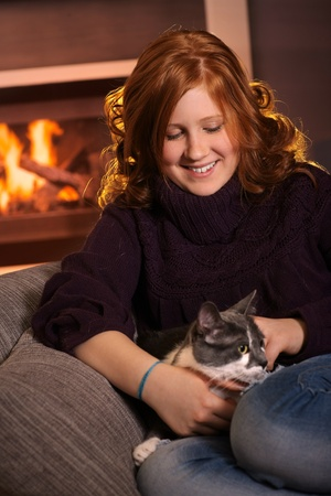 Happy teenage girl sitting at fireplace at home fondling cat smiling. photo