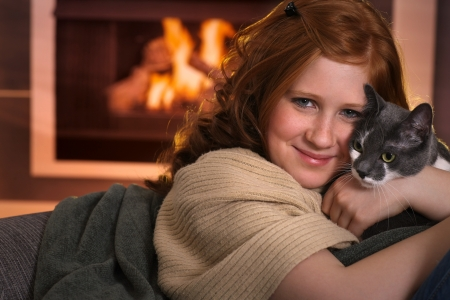 Teenage girl sitting at fireplace at home cuddling cat smiling. photo