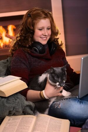 Smiling teenage girl sitting at fireplace at home learning with laptop and books. Happy brainy preoccupation. photo
