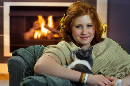 Teenage girl sitting at fireplace fondling cat. photo