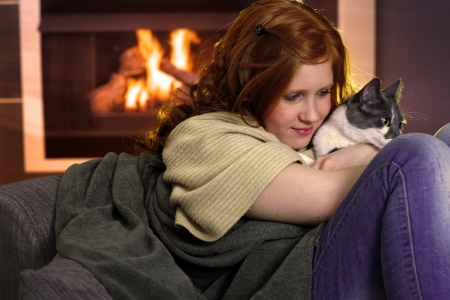 fondling: Red hair teenager girl fondling cat at home sitting by fireplace.