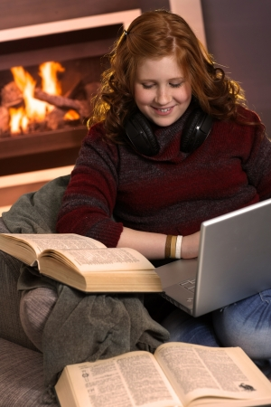 Redhead teenager girl learning at home with books and laptop, happy smile. photo