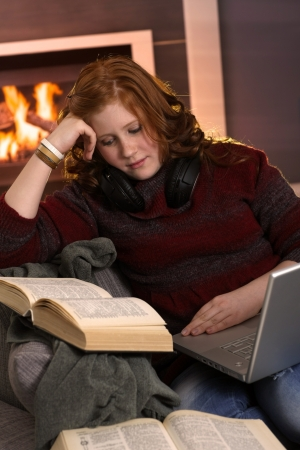 Redhead teenager girl learning at home with books and laptop, serious expression. photo