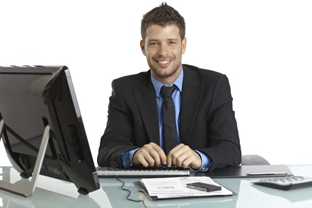 Happy young businessman sitting at desk, working, looking at camera. photo