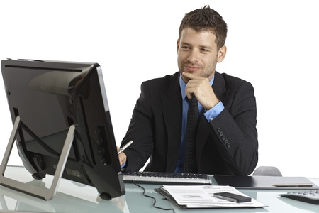 Young businessman working with computer, smiling. photo