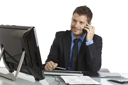 Busy businessman sitting at desk, using mobilephone and computer. photo