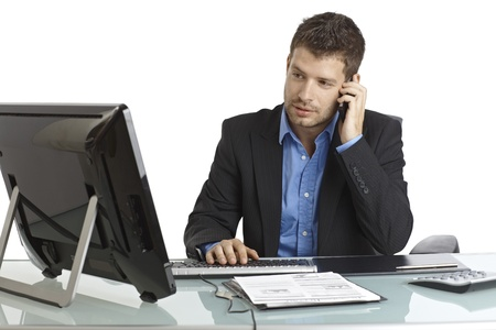 agente comercial: Hermoso joven empresario sentado en el escritorio, usando la computadora y teléfono móvil. Foto de archivo