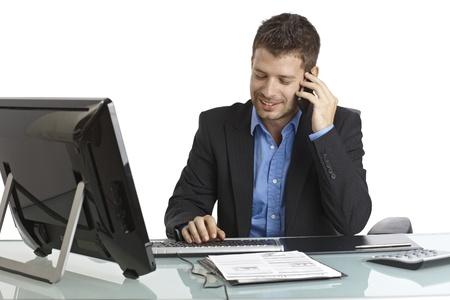 Young businessman sitting at desk, talking on mobilephone, typing on keyboard, smiling. photo