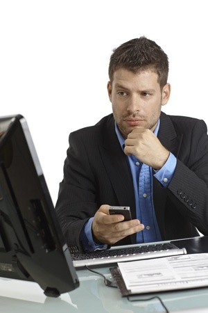 Young businessman sitting at desk, looking at screen, starting phone call. photo