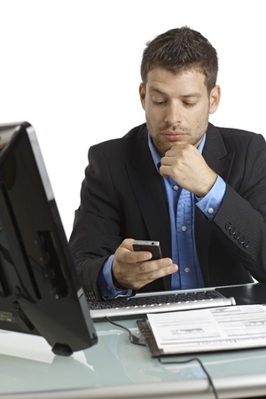 Young businessman sitting at desk, working with computer and mobilephone. photo