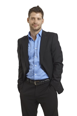 Confident young businessman standing with hands in pockets. photo