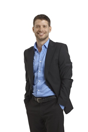 stubbly: Happy young businessman standing with hands in pockets. Stock Photo