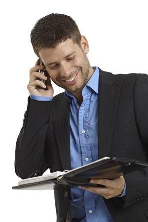 Happy young businessman talking on mobilephone, holding organizer. Stock Photo - 15965748