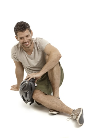 Young smiling man holding helmet, sitting on floor, smiling. photo