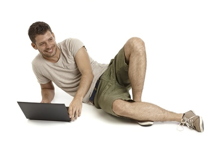 lying on side: Young man lying on side, using laptop computer, looking away, smiling.