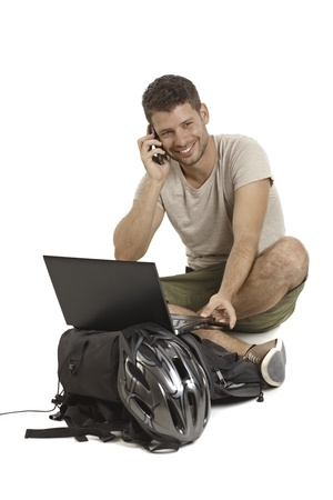 tailor seat: Young man sitting in tailor seat, using laptop computer, talking on mobilephone, having helmet and backpack, smiling. Stock Photo