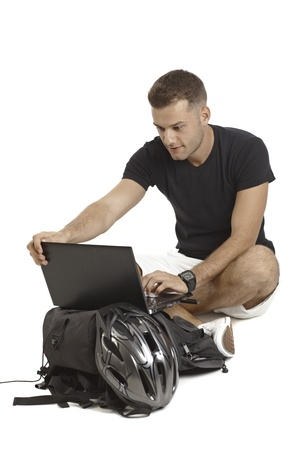 helmet seat: Casual young man using laptop computer, having backpack and helmet, sitting in tailor seat.