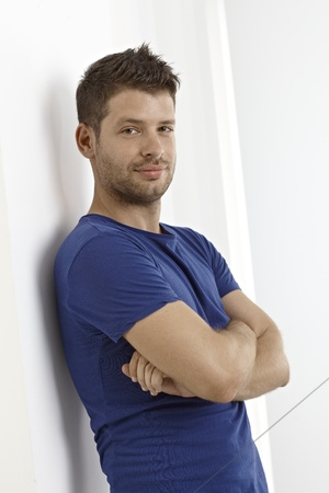 bristly: Confident young man standing arms crossed, smiling. Stock Photo